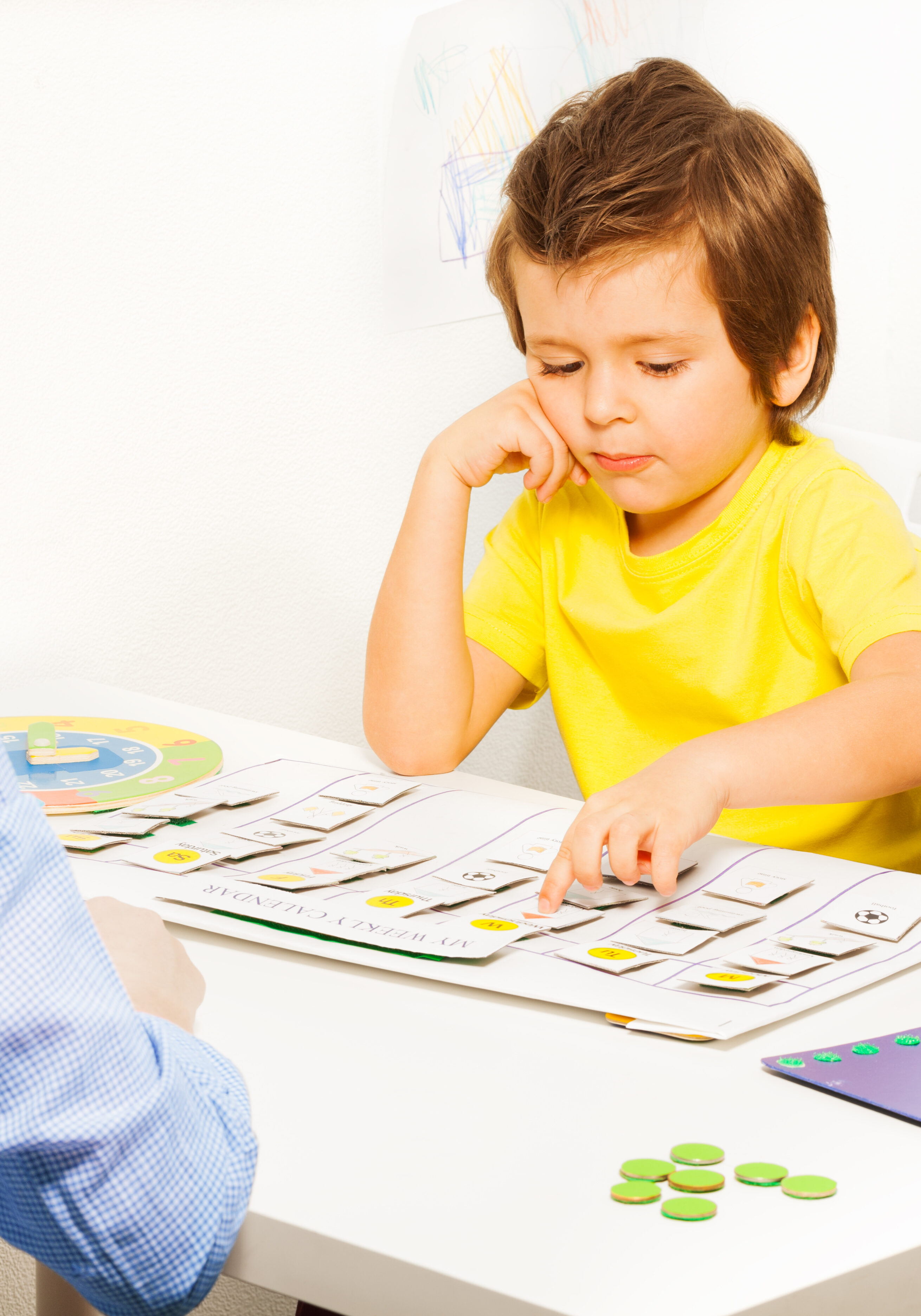 Boy pointing at colorful day activities cards on calendar during developing game with his parent sitting opposite at the table in the room